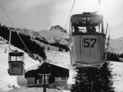The construction of the first continuous movement monocable gondola lift with 4-passenger cabins marked a major event in the company's history and the first time it had used detachable grip technology. The red gondolas on the lift in Mellau, Bregenzerwald (Austria), were fitted with ski holders; the doors were manually opened and closed to allow passengers to load and unload in the stations.